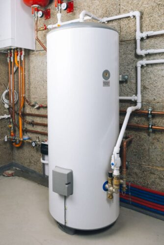 white storage tank water heater in boiler room