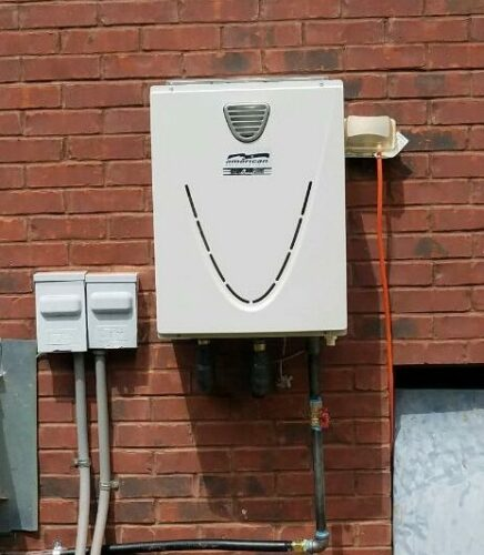 gray tankless water heater installed outside on a brick wall of the building