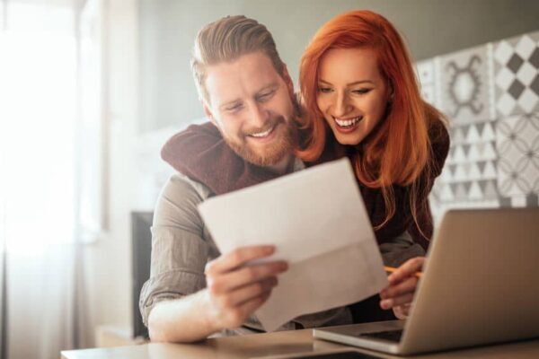 young happy couple smiling at their reduced heating bill