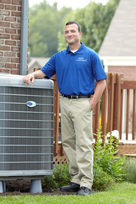 hvac tech posing next to a carrier ac unit outside in henderson tn