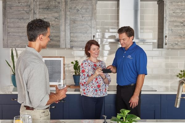 hvac technician showing husband and wife thermostat controls on phone in medina tn