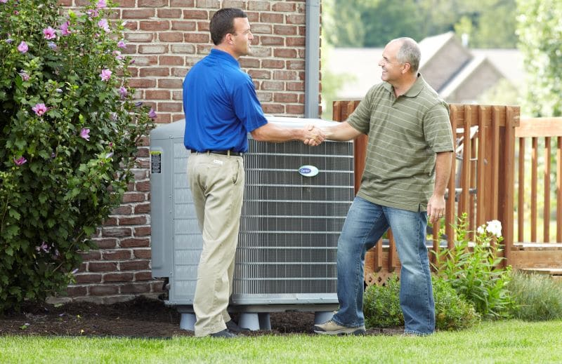 homeowner shaking hands with hvac technician next to carrier ac unit in brownsville tn