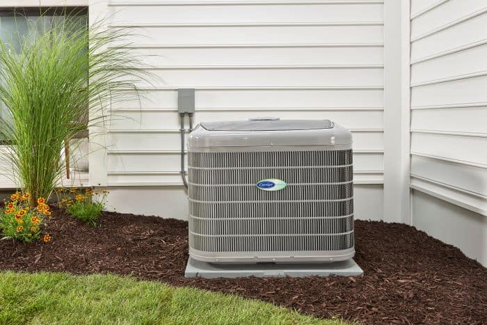 air conditioner located outside in yard next to white house