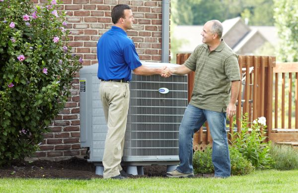 hvac technician setting up maintenance agreement with man outside of house
