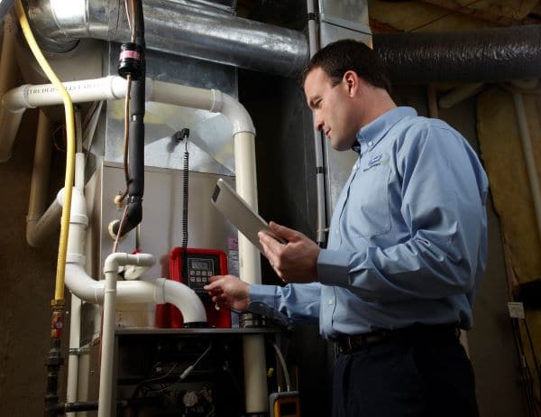 man performing furnace maintenance with an fall hvac maintenance checklist