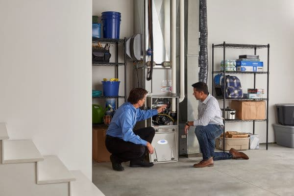 two men in garage discussing the cost of a furnace